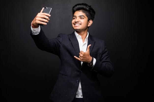 Hombre joven sonriente que toma la foto del selfie en smartphone. chico indio con dispositivo digital. concepto de foto selfie. vista frontal aislada en la pared negra.