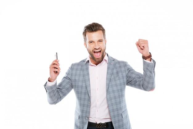 El hombre joven sonriente que usa el teléfono móvil hace gesto del ganador.