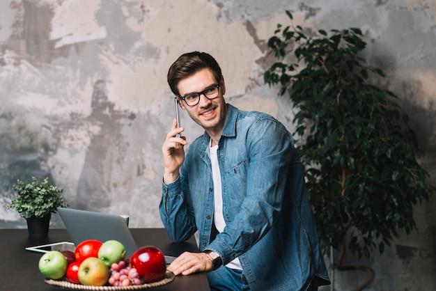 Hombre joven sonriente que usa el teléfono móvil con el ordenador portátil y las frutas