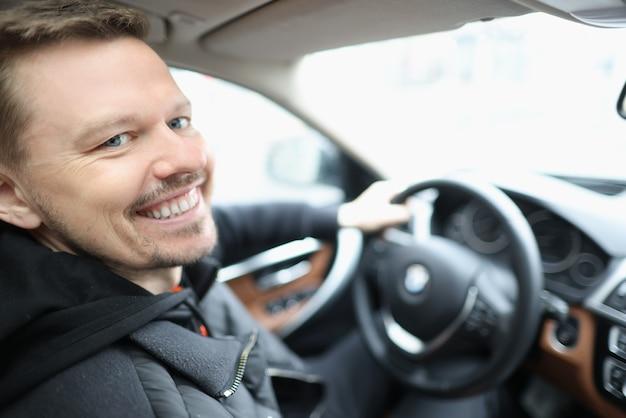 Hombre joven sonriente se sienta en el salón del coche detrás del volante