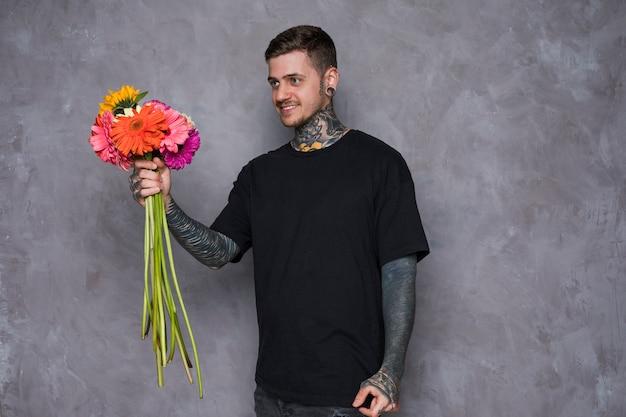 Hombre joven sonriente con el tatuaje en su cuerpo que ofrece las flores del gerbera contra la pared gris