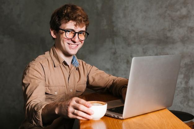 Hombre joven con la sonrisa de la computadora portátil