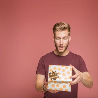 Hombre joven sorprendido que abre la caja de regalo floral con el arco de oro
