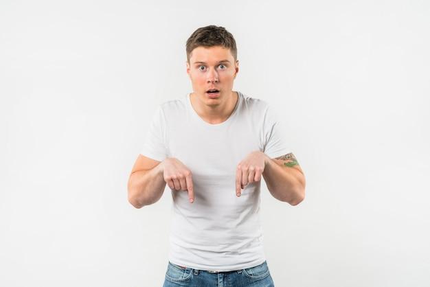 Hombre joven sorprendido que señala sus dedos hacia abajo contra el fondo blanco