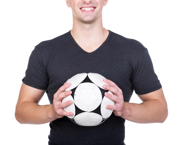 El hombre joven está sosteniendo un balón de fútbol