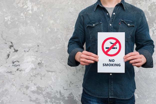 Hombre joven sosteniendo un cartel de texto y cartel de no fumar sobre la pared vieja
