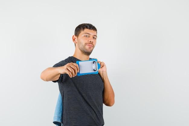 Hombre joven sosteniendo la chaqueta mostrando mini portapapeles en camiseta y mirando alegre