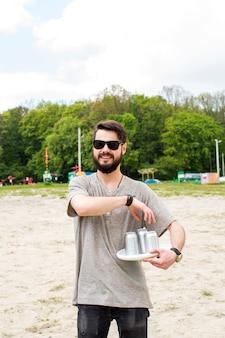 Hombre joven sosteniendo latas de cerveza
