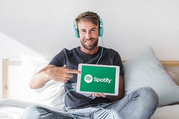 Hombre joven sosteniendo tablet con la app de spotify