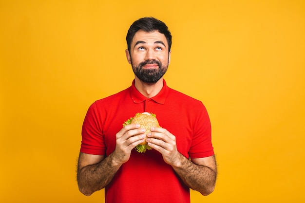 Hombre joven sosteniendo un trozo de sándwich. el estudiante come comida rápida. la hamburguesa no es comida útil.