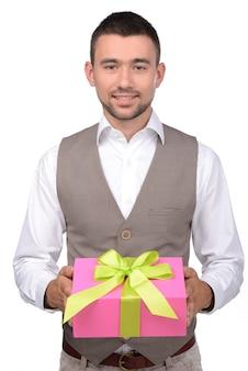 El hombre joven sostiene una caja con un regalo.