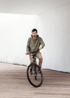 Hombre joven con su bicicleta en un túnel