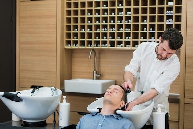 Hombre joven con su cabello lavado en una peluquería