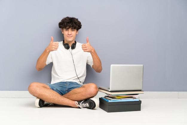 Hombre joven con su computadora portátil sentado uno el piso dando un gesto de pulgares arriba