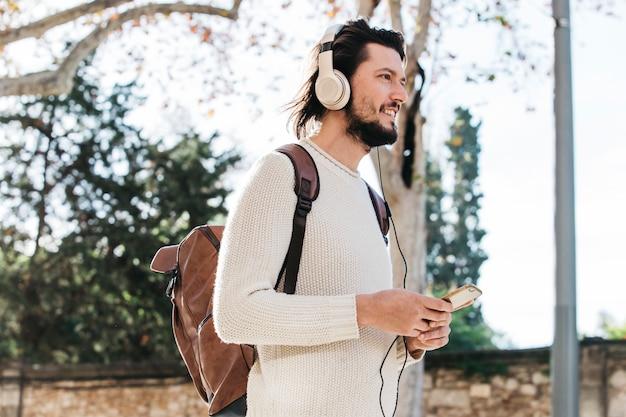 Hombre joven con su música que escucha de la mochila en el teléfono celular a través de los auriculares en el aire libre