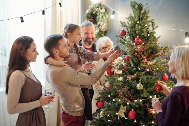 Hombre joven con su pequeña hija y otros miembros de la familia de pie junto al árbol de navidad en casa mientras se prepara para las vacaciones