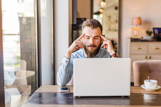 Hombre joven subrayado que se sienta en café con el ordenador portátil en el escritorio