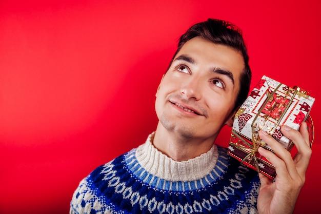 Hombre joven en suéter islandés sosteniendo una caja de regalo. concepto de celebración de navidad.