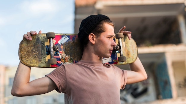 Hombre joven sujetando patineta