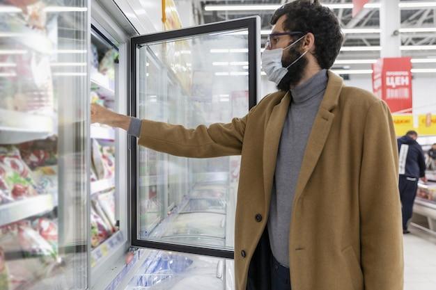 Hombre joven en el supermercado en el departamento de congelación.