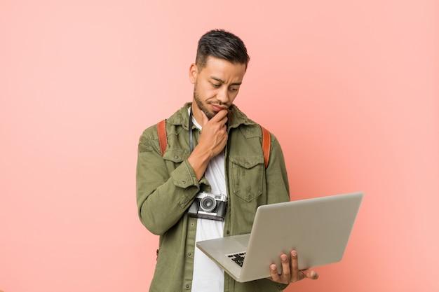 Hombre joven del sur de asia que sostiene una computadora portátil.