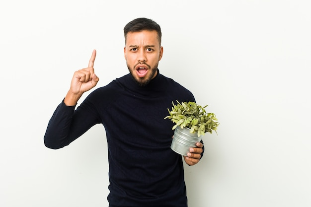 Hombre joven del sur de asia sosteniendo una planta que tiene una idea, concepto de inspiración.