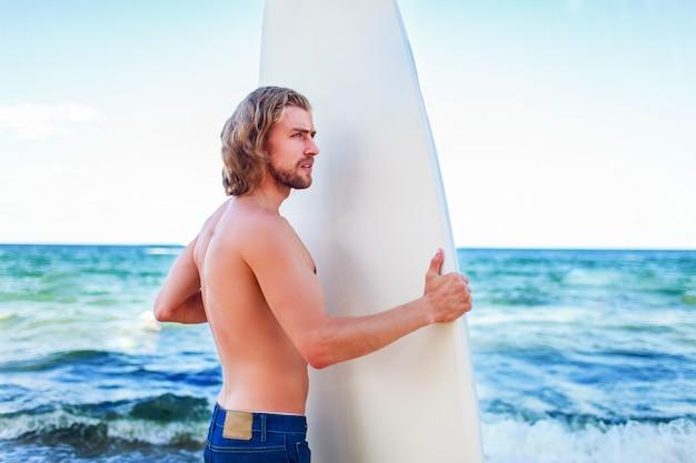 Hombre joven surfista atractivo con el pelo largo con jeans
