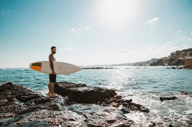 Hombre joven con tabla de surf en piedra cerca del agua