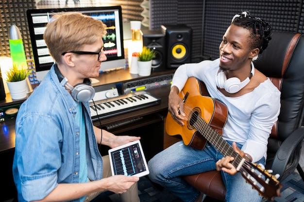 Hombre joven con tableta digital hablando con un colega feliz con guitarra mientras ambos están sentados en el lugar de trabajo en el estudio de grabación de sonido
