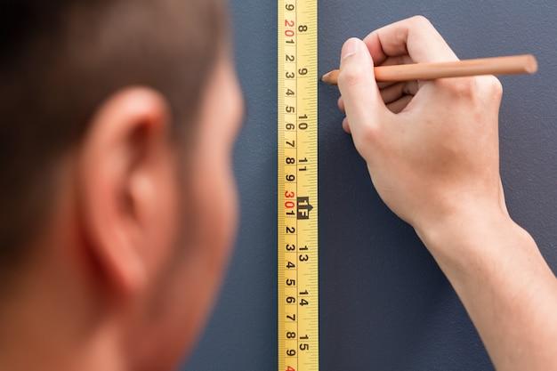 Hombre joven de tamaño con cinta métrica