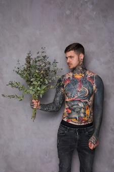 Hombre joven tatuado descamisado en su cuerpo y piercing en sus oídos y nariz mirando a la cámara