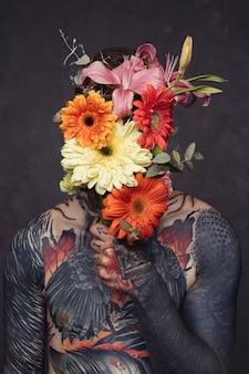 Hombre joven tatuado con oreja perforada y nariz sosteniendo un ramo de flores frente a su cara
