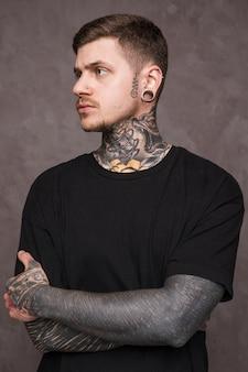 Hombre joven tatuado con piercing en sus orejas y nariz con el brazo cruzado mirando a otro lado