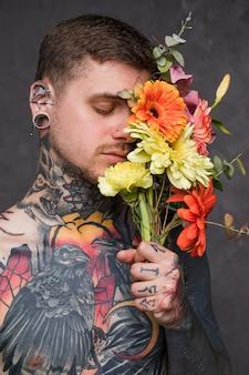 Hombre joven con tatuado en su cuerpo sosteniendo la flor en la mano