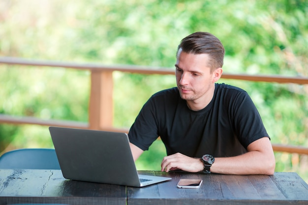 Hombre joven con teléfono celular al aire libre en la cafetería al aire libre. hombre con teléfono inteligente móvil.