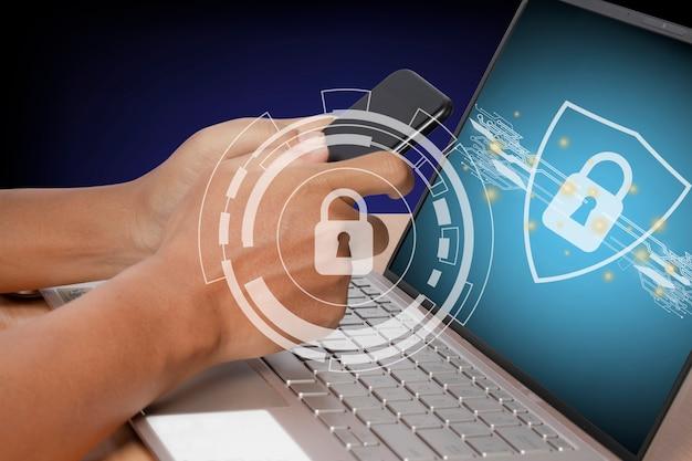 Hombre joven con un teléfono inteligente y una computadora portátil. sistema de seguridad de internet cibernético. bloquear la tecnología de seguridad del icono en la pantalla del ordenador portátil.