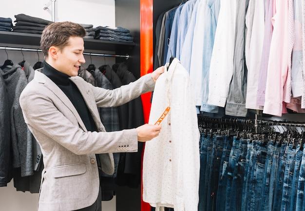Hombre joven en la tienda que controla un precio en la camisa