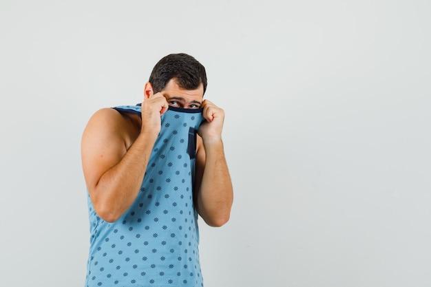 Hombre joven tirando del cuello en la cara en camiseta azul y mirando asustado, vista frontal.