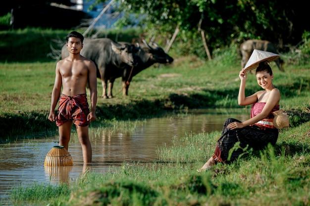 Hombre joven en topless de pie y sosteniendo una trampa de pesca de bambú para pescar peces para cocinar con una hermosa mujer sentada cerca del pantano