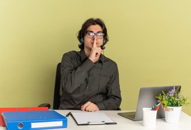 Hombre joven trabajador de oficina ansioso en auriculares con gafas ópticas se sienta en el escritorio con herramientas de oficina usando laptop pone el dedo en la boca gesticulando silencio aislado sobre fondo verde con espacio de copia