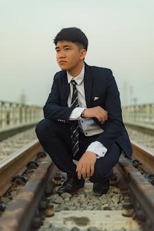 Hombre joven en un traje agachado en medio de un ferrocarril mirando a otro lado