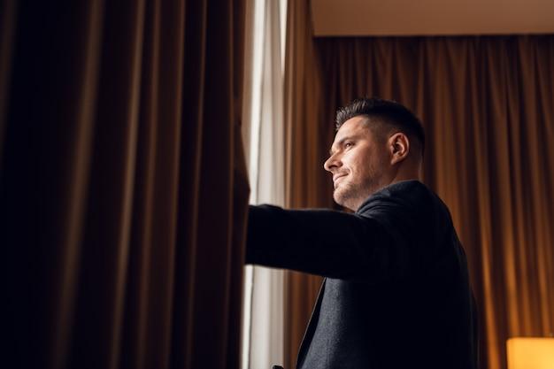 Un hombre joven en traje formal separando las cortinas de su dormitorio para dejar entrar la luz de la mañana