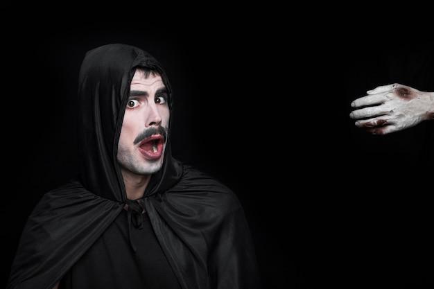 Hombre joven en traje de halloween con cara asustada y mano del cadáver