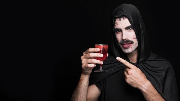 Hombre joven en traje de halloween con copa de vino