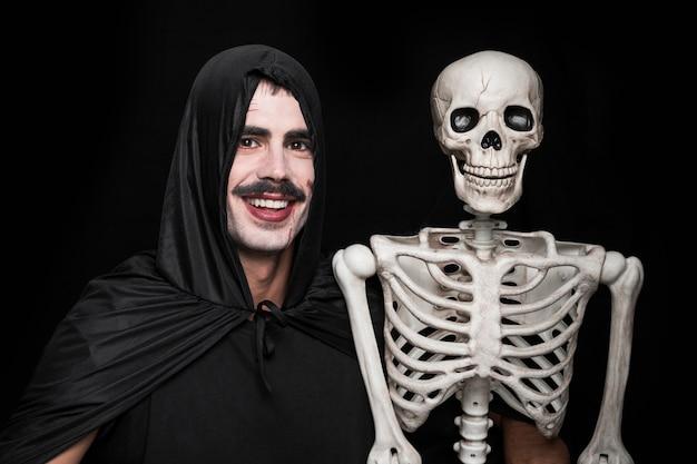 Hombre joven en traje de halloween posando en estudio con esqueleto