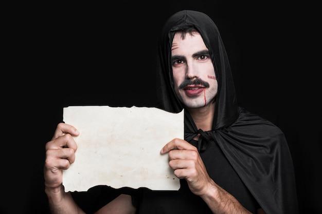 Hombre joven en traje de halloween posando en estudio con papel