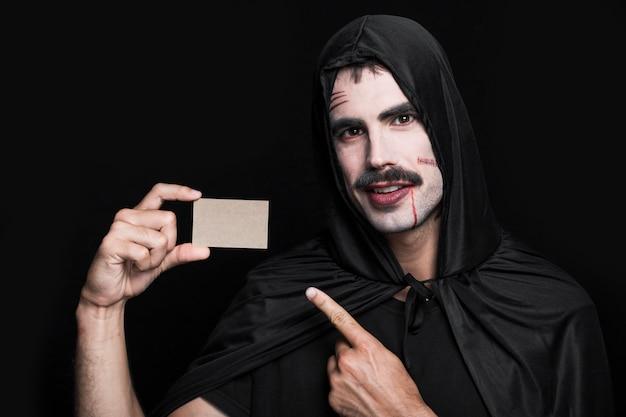 Hombre joven en traje de halloween posando en estudio con pedacito de papel