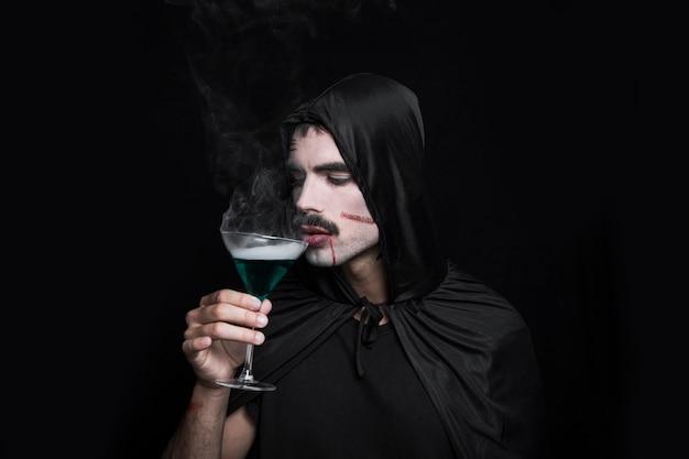 Hombre joven en traje de halloween posando en estudio con vidrio