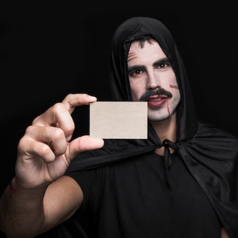 Hombre joven en traje negro de halloween que muestra poca tarjeta de papel en blanco