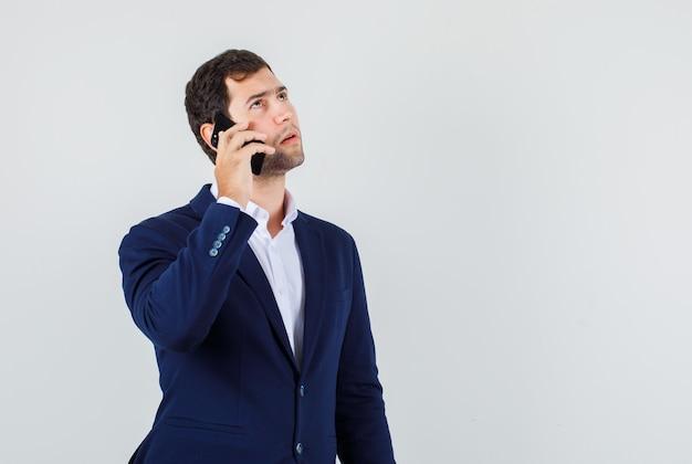 Hombre joven en traje pensando mientras habla por teléfono inteligente y mirando serio, vista frontal.